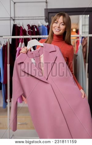 Young girl with a coat in the shop