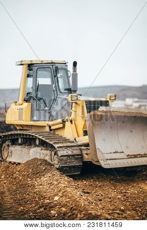 Industrial Yellow Bulldozer Leveling Earth And Gravel