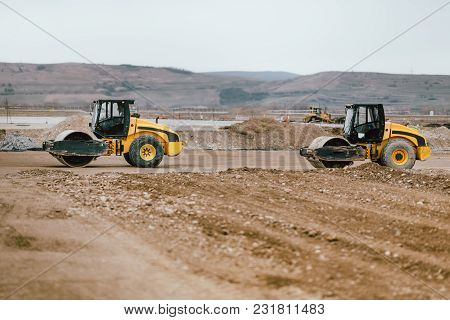 Two Vibratory Soil Compactors During Road And Highway Construction. Industrial Roadworks With Heavy-