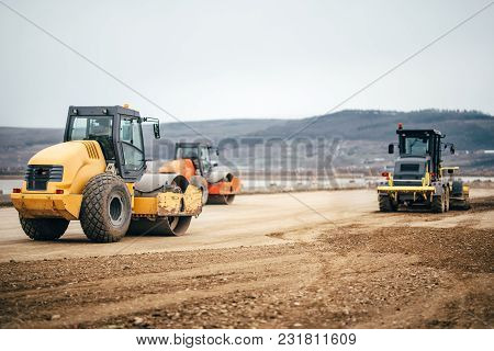 Vibratory Soil Compactors On Highway Construction Site. Industrial Roadworks With Heavy-duty Machine