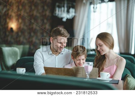 Smiling family with menu in a restaurant