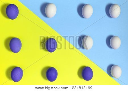 White And Brown Violet Ggs On Blue And Yellow Pastel Background, Copy Space. Boiled Eggs On Paper Ba