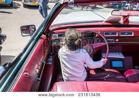 Beit Nir, Israel - March 17, 2018: Little Girl Sit In Vintage Cadillac Eldorado Car, Presented On Ol