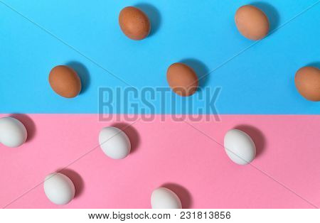 White And Brown Eggs On Blue And Pink Pastel Background, Copy Space. Boiled Eggs On Paper Background