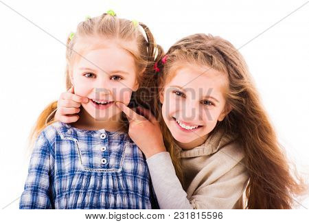 Girl put her fingers to the corners of the mouth to make her little sister smile. Two sisters having relaxing time together isolated on white background