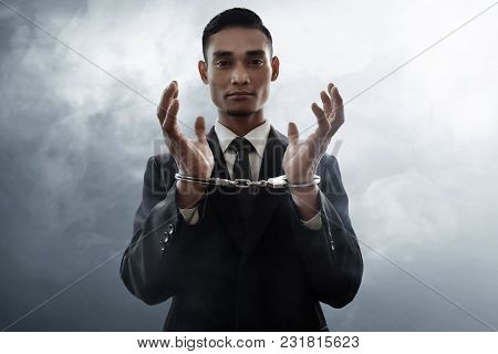 Asian Businessman In Handcuffs On Smoke Background
