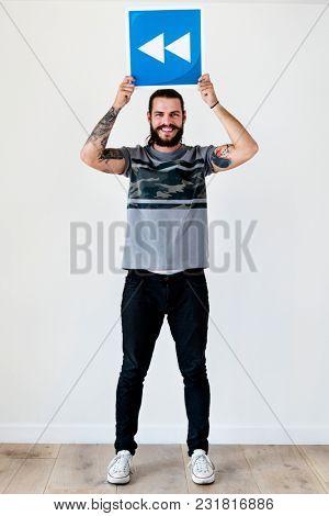 Caucasian guy holding backward icon