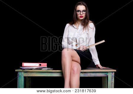 Sexy Teacher Posing On Desk In Studio On Black Background.