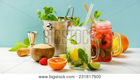 Fresh cocktail drinks with ice fruit and herb decoration. Alcoholic non-alcoholic drink-beverage. Mojito on blue background