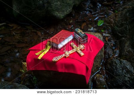 Holy Bible and the Orthodox Cross during the sacrament of baptism, outdoors.
