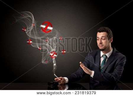 Businessman smoking with colored no smoking symbols nearby.