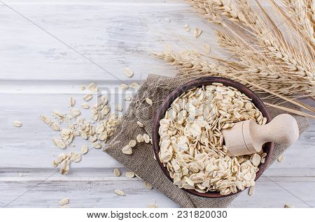 Oat Flakes  In Ceramic Bowl And Wooden Spoon And Spikelets On White Vintage Wooden Background, Selec