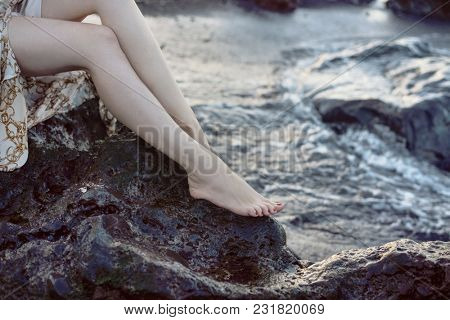Woman's legs on stony beach