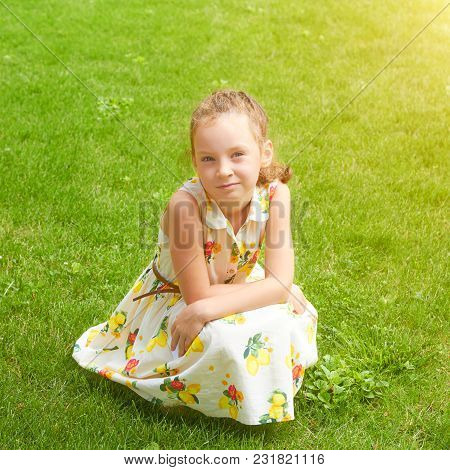 Little Beautiful Girl In Dress On The Green Grass In The Park