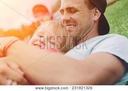 Young Father Hugging His Cute Daughter. Happy Family Time, Intentional Sun Glare