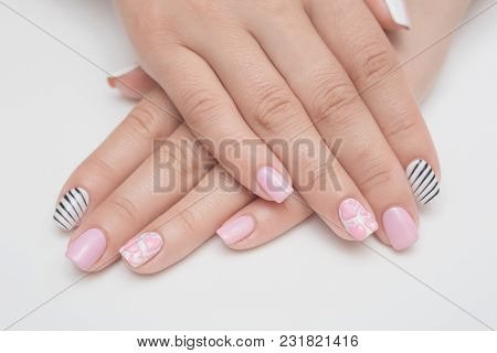 Manicure with rhinestones in the shape of hearts and pink balls on white and red nail Polish on a white background. poster