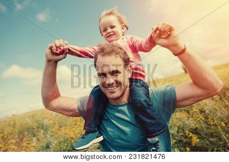 Father Running In The Field With His Daughter On The Shoulders, Intentional Sun Glare