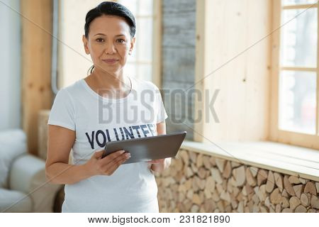 Technology In Volunteering. Focused Pensive Female Volunteer Standing On Blurred Background And Hold