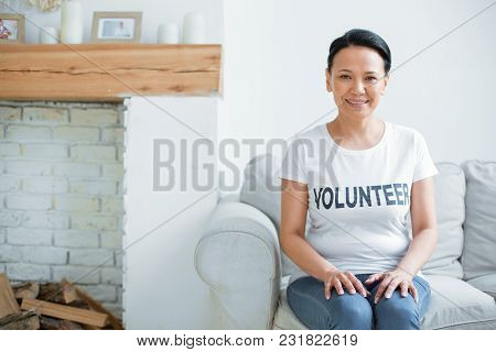 Volunteer Days. Gay Optimistic Female Volunteer Gazing At Camera And Sitting On Couch While Putting