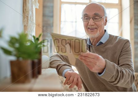 Family Photo. Charming Calm Senior Man Holding Photo Frame While Wearing Glasses And Smiling