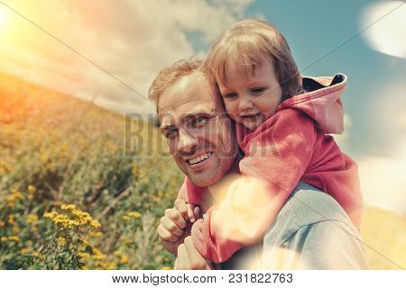 Young Father Playing With His Cute Baby Outdoors, Intentional Sun Glare And Lens Flares
