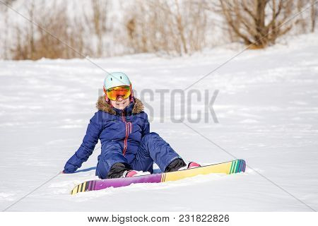 Picture Of Athlete In Helmet With Snowboard Sitting On Snowy Hill On Winter Day