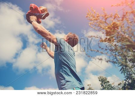 Father Playing And Catching His Daughter In The Field Outdoors, Intentional Sun Glare