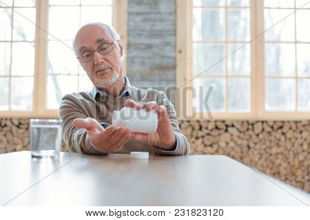 Support Your Health. Calm Confident Senior Man Wearing Glasses While Placing Pills In Hand And Stari