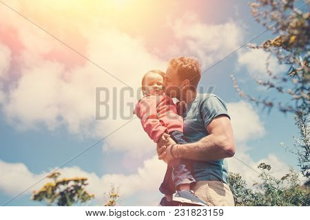 Young Father Holding And Kissing His Cute Daughter, While Spending Time Outdoors, Intentional Sun Gl