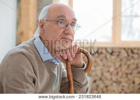 Long Life. Thoughtful Pensive Senior Man Dreaming While Leaning On Cane And Putting On Glasses