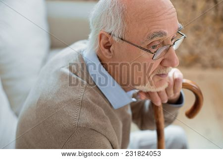 No Rush. Attentive Focused Senior Man Sitting In Profile While Leaning On Cane And Dreaming