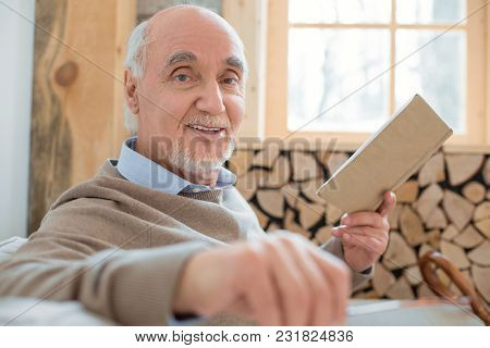 Amazing Book. Jovial Optimistic Senior Man Smiling While Holding Book And Looking At Camera