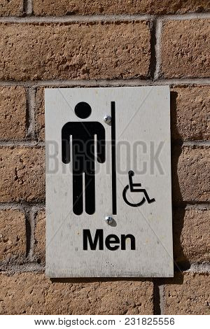 A Sign On A Brick Wall Indicates A Mens Room With Handicap Access