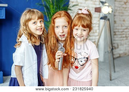 Three Kids Sing A Song In A Microphone. Group. The Concept Is Childhood, Lifestyle, Music, Singing,