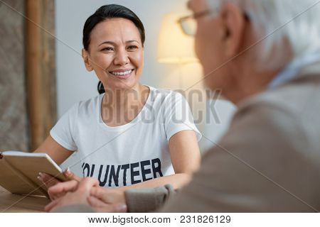 Wise Thought. Jolly Joyful Volunteer Grinning While Holding Notebook And Staring At Senior Man