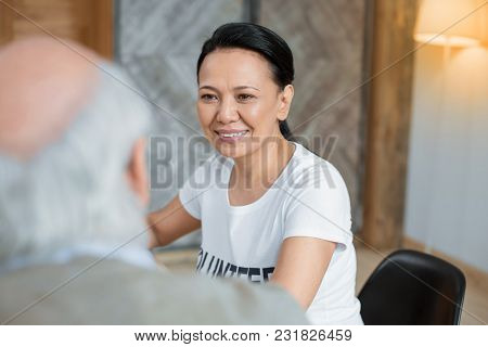 Minute For Story.. Appealing Glad Volunteer Grinning While Sitting On Blurred Background And Listeni