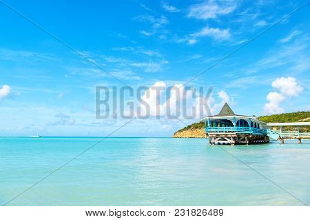 Sea Beach With Wooden Shelter On Sunny Day In Antigua. Pier In Turquoise Water On Blue Sky Backgroun