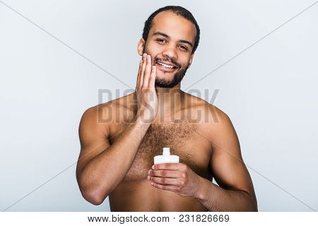 Cream That Gives Relief. Portrait Of Handsome Shirtless Young Black Man Using Lotion And Looking At