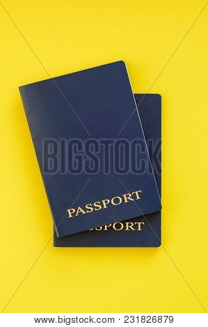Two Blue Passports On A Yellow Background. Top View
