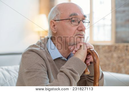 Depressive Mood. Handsome Reflective Senior Man Leaning On Cane While Wearing Glasses And Posing On