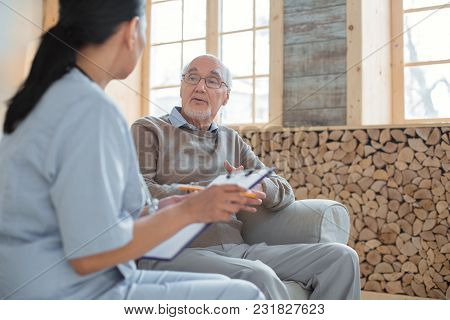 My Complaints. Doctor Holding Clipboard While Taking Notes And Talking To Experienced Smart Senior M