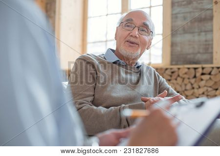 At My Age. Doctor Using Clipboard While Taking Notes And Listening To Glad Pleasant Senior Man