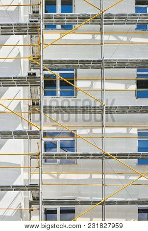 scaffolding near a new house under construction, white wall and window, yellow pipe