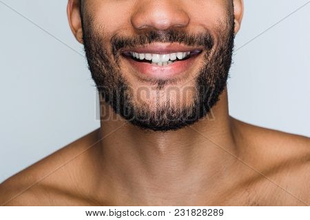 Cheerful Smile. Close Up Part Of Handsome Young Black Man Smiling While Standing Against White Backg