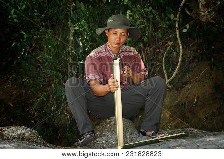 Nha Trang,khanh Hoa,vietnam -april 23, 2014  Vietnamese Man Treats A Bamboo Trunk With A Sickle-shap
