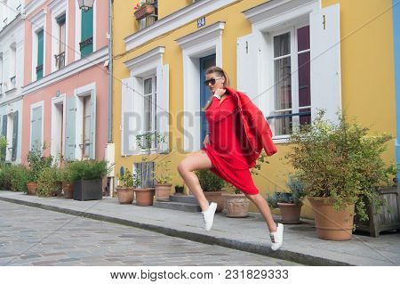 Sexy Woman Jump On Street Of Paris, France, Vacation. Woman In Sunglasses, Red Dress, Sneakers On St