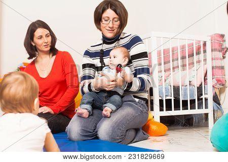 Four Moms With Their Lovely Children In Kindergarten