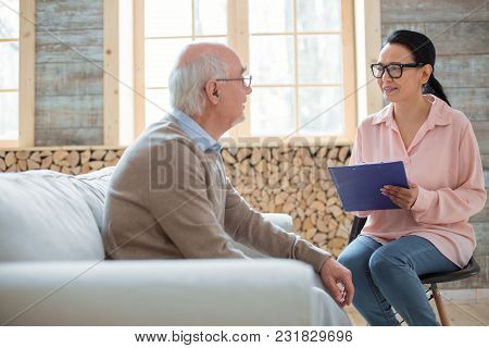 Duties Of Caregiver. Appealing Glad Caregiver Using Clipboard While Wearing Glasses And Talking To S