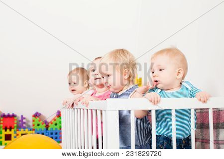 Group Of Little Babies Are Stand Up In The Crib, Day Care Center