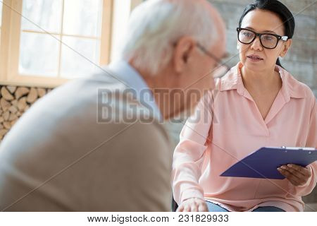 Responsibility Of Caregiver. Appealing Asian Caregiver Holding Clipboard While Wearing Glasses And C